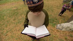 A young student prays with his sidur outside